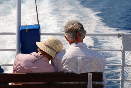 Tilos, Greece - June 12, 2010 -  A couple sitting at the stern of a catamaran ferry boat  near the Greek island of Tilos. Stock Photo - 7659768