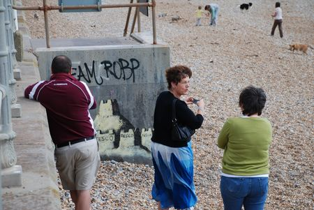 pseudonym: St. Leonards-on-Sea, England - August 28, 2010 -  Members of the public photograph a new mural by cult British street artist