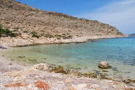 halki: The pebble beach at Kania on the Greek island of Halki. Stock Photo
