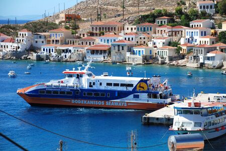 halki: Emborio, Greece - June 7, 2010 - Catamaran ferry boat Dodekanisos Express departs from the harbour on the Greek island of Halki.