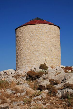 halki: An old stone windmill on the hill above Emborio on the Greek island of Halki. Stock Photo
