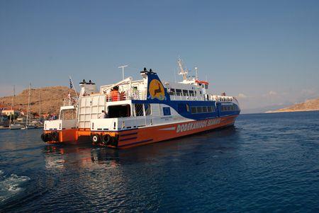 emborio: Emborio, Greece - June 12, 2010 - Catamaran ferry boat Dodekanisos Express departs from Emborio harbour on the Greek island of Halki.