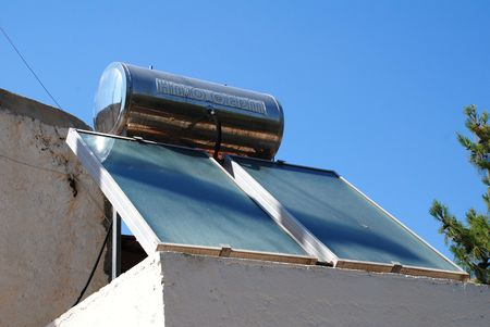Emborio, Greece - June 13, 2010 - Solar heating panel and water tank on the roof of a building on the Greek island of Halki.