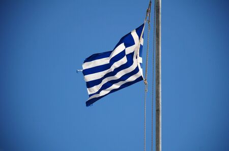 halki: The Greek national flag flying at Emborio harbour on the Greek island of Halki.