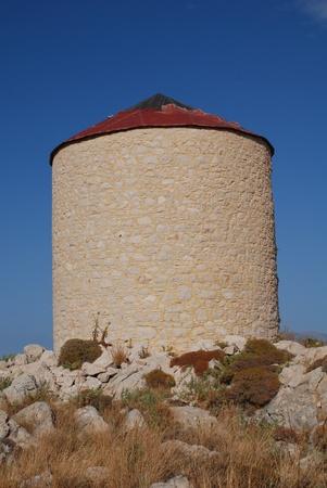 halki: An old stone windmill on the hills above Emborio on the Greek island of Halki.