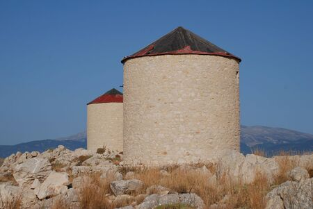 halki: Old stone windmills on the hill above Emborio on the Greek island of Halki.