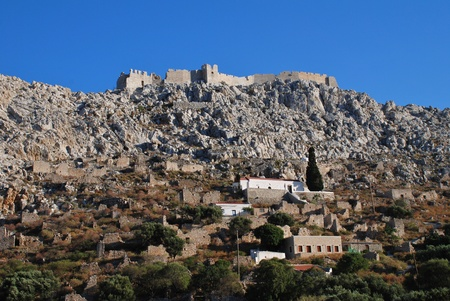 halki: The mainly abandoned village of Horio showing the Church of the Panagia and the crusader castle above, on the Greek island of Halki.