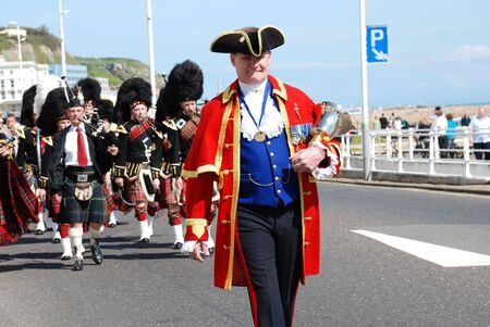 Hastings, England - April 26, 2009 - John Bartholomew, Town Crier, leads the 1066 Pipes & Drums band along the seafront during a St.Georges Day parade.