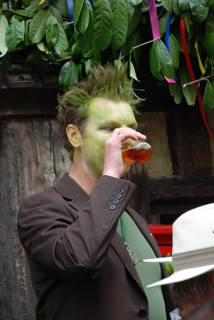 daubed: Hastings, England - May 5, 2009 - A man with a green painted face drinks a beer during the annual Jack In The Green festival. Editorial