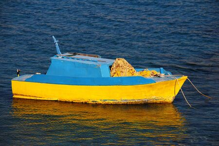 halki: A blue and yellow wooden fishing boat moored off Pondamos beach at Emborio on the Greek island of Halki.