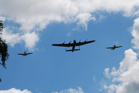 Tenterden, England - May 14, 2011 - The Battle of Britain Memorial Flight, consisting of a Lancaster bomber flanked by Spitfire and Hurricane fighters, give a display over Tenterden, Kent.