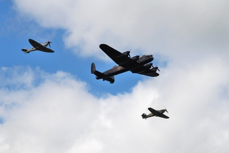 Tenterden, England - May 14, 2011 - The Battle of Britain Memorial Flight, consisting of a Lancaster bomber flanked by Spitfire and Hurricane fighters, give a display over Tenterden, Kent. Stock Photo - 9587717