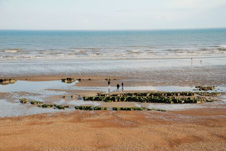 Hastings, England - April 25, 2009 - People walking on the beach at low tide at Hastings in East Sussex. Stock Photo - 9891734