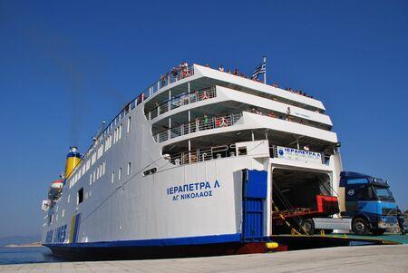 emborio: Halki, Greece - June 14, 2010 - ANEK Lines ship Iearapetra L. unloads at Emborio harbour on the Greek island of Halki. Founded in 1967 ANEK now operates a fleet of eleven ships.