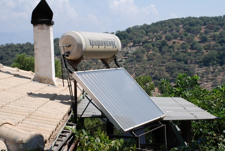 Meganissi, Greece - August 31, 2008 - A solar heating panel and water tank on a roof top at Spartohori on the Greek island of Meganissi.