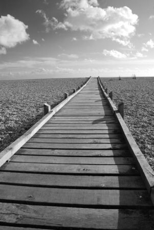 kent: A wooden boardwalk across the pebble beach at Dungeness in Kent, England. Stock Photo