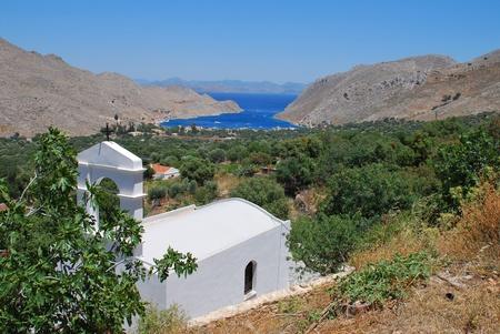 vale: Symi, Grecja - 27 czerwca 2011 - mała kapliczka stoi nad Vale of Pedi na greckiej wyspie Symi. Publikacyjne