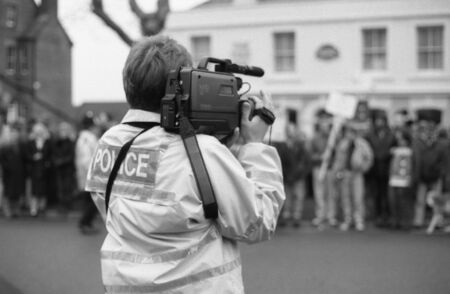 protestors: Tenterden, England - December 26, 1992 - A police officer films anti hunt protestors demonstrating in the High Street againt the Boxing Day meet of the Ashford Valley Hunt. Fox hunting was outlawed in England and Wales in November 2004.