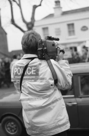 Tenterden, England - December 26, 1992 - A police officer films anti hunt protestors demonstrating in the High Street againt the Boxing Day meet of the Ashford Valley Hunt. Fox hunting was outlawed in England and Wales in November 2004. Stock Photo - 11748911