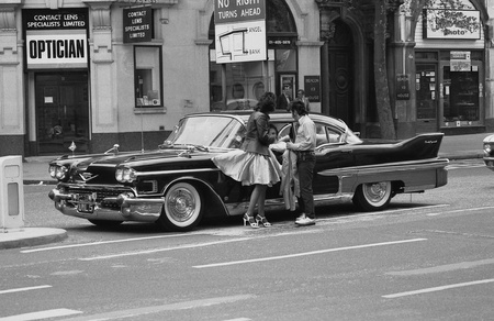 50s fashion: London, England - May 15, 1976 - Music fans admire a vintage American car during the Rock and Roll Radio Campaign march. The campaign called for more vintage Rock and Roll music to be played on British radio.