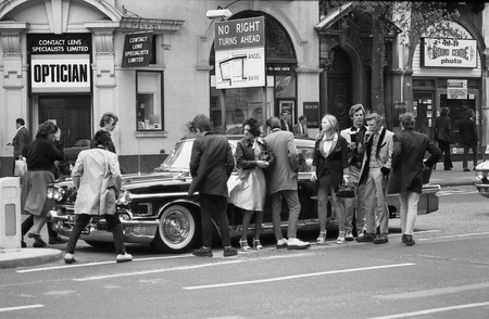 London, England - May 15, 1976 - Music fans admire a vintage American car during the Rock and Roll Radio Campaign march. The campaign called for more vintage Rock and Roll music to be played on British radio. Stock Photo - 12059760