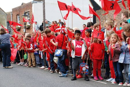 Rye, England - July 18, 2012 - Children line the streets waiting to see the Olympic Torch Relay.