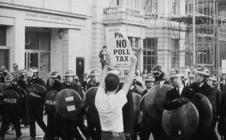 protestor: London, England - March 31, 1990 - A protestor hold up a banner in front of riot police in St.Martins Place during the Poll Tax Riots. Editorial