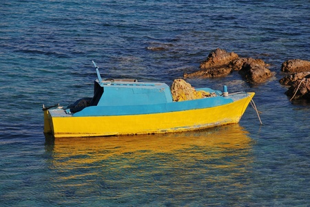 halki: A small yellow and blue fishing boat moored off Emborio on the Greek island of Halki