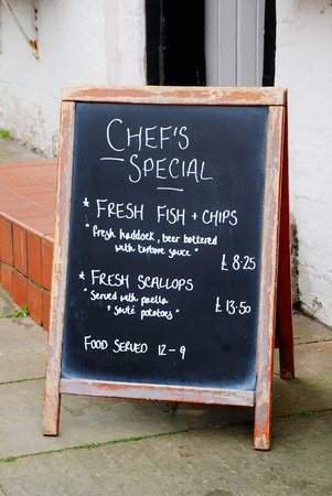 A blackboard menu sign advertising food outside a pub at Rye in East Sussex, England  photo
