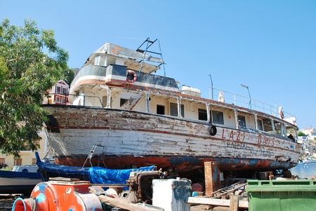 former years: Symi, Greece - June 18, 2011 - Lazy Days, a former excursion boat, lays crumbling in the Harani boatyards at Yialos on the Greek island of Symi  The boat has been there for some nineteen years following an ownership dispute