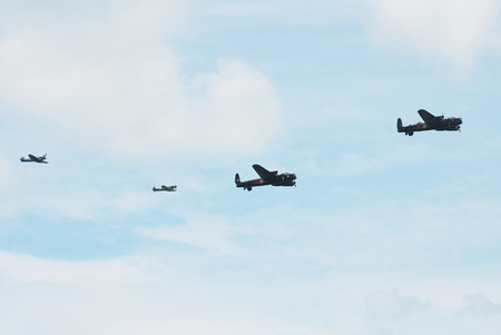 Eastbourne, England - August 14, 2014 - Lancaster bomber PA474 (front) of the Battle of Britain Memorial Flight with Lancaster KB726 of the Canadian Warplane Heritage Museum and Spitfire and Hurricane fighters display at the Airbourne airshow.