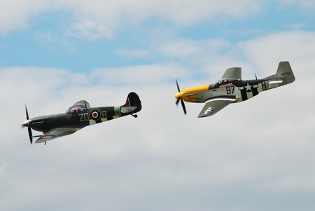 Dunsfold, England - August 23, 2014 - Spitfire Mk 1XB, MH434 and Mustang P-51D, Ferocious Frankie perform at the Dunsfold airshow. Both aircraft served in the Second World War.