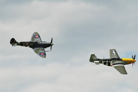 Dunsfold, England - August 23, 2014 - Mustang P-51D Ferocious Frankie and Spitfire Mk 1XB, MH434, perform at the Dunsfold airshow. The two aircraft both served in the Second World War.