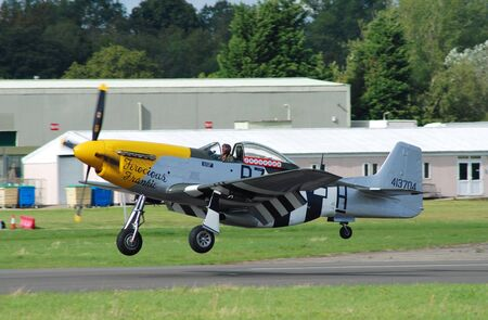 Dunsfold, England - August 23, 2014 - Mustang P-51D fighter Ferocious Frankie landing during the Dunsfold airshow. The aircraft was built in 1944 before serving in the US Air Force.