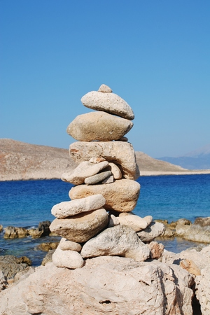 halki: A pile of stones on Ftenagia beach at Emborio on the Greek island of Halki. The uninhabited island of Nissos is in the background.