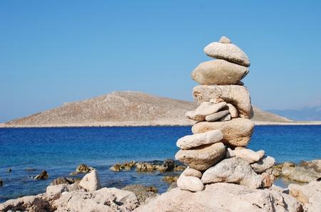 emborio: A pile of stones on Ftenagia beach at Emborio on the Greek island of Halki. The uninhabited island of Nissos is in the background.