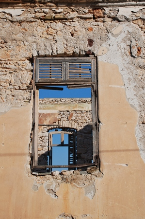halki: Looking through the windows of a derelict building at Emborio on the Greek island of Halki.