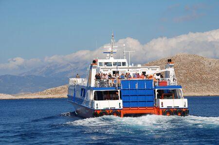 emborio: Halki, Greece - June 9, 2015 - Dodekanisos Seaways high speed catamaran Dodekanisos Express heads past Nissos island whilst departing Emborio harbour on the Greek island of Halki. The 40mtr vessel was built in Norway in 2000.