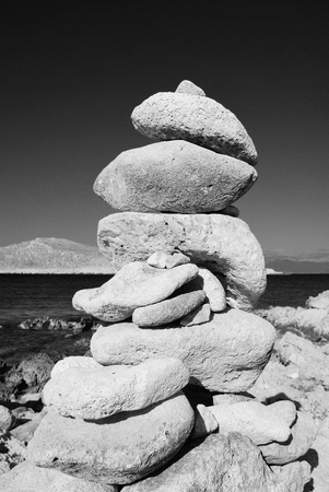 halki: A tower of stones standing on Ftenagia beach at Emborio on the Greek island of Halki.