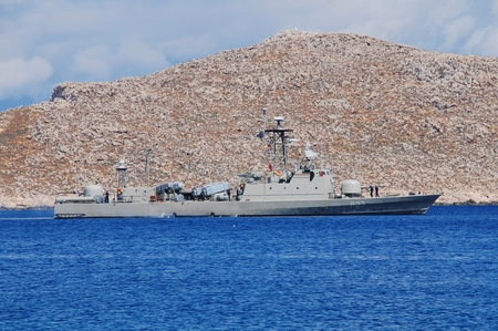 emborio: Halki, Greece - June 10, 2015 - Hellenic Navy Combattante 111N class patrol boat Antipliarchos Mykonios, P23, departs Emborio harbour. The French built missile boat first entered service in 1978.