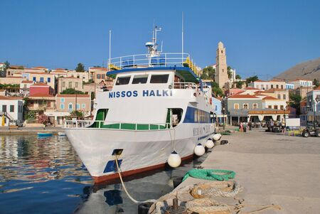 halki: Halki, Greece - June 17, 2015 - Passenger ferry Nissos Halki moored in Emborio harbour on the Greek island of Halki. The 29mtr vessel operates between Kamiros Skala harbour in Rhodes and Halki island.