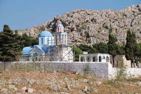 emborio: The blue domed church in the cemetery at Emborio on the Greek island of Halki. The bell tower is supported by scaffold due to structural damage.