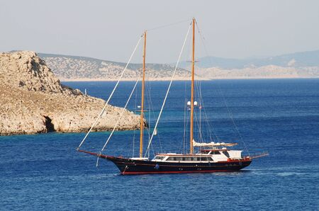 halki: A twin masted sailing boat enters the harbour at Emborio on the Greek island of Halki.