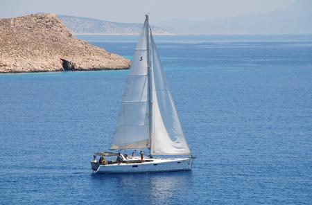 emborio: Halki, Greece - June 14, 2015 - A sailing yacht departs from Emborio harbour on the Greek island of Halki. The small island near Rhodes is a popular destination for the sailing community. Editorial