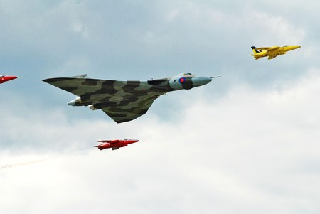 escorted: Dunsfold, England - August 23, 2014 - Avro Vulcan XH588 is escorted by the Gnat Display Team during the annual Dunsfold airshow. Built in 1960, XH588 is the last flying Vulcan bomber.