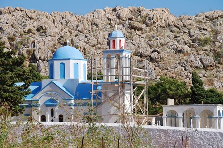 halki: The domed church at Emborio cemetery on the Greek island of Halki. The bell tower is supported by scaffolding due to structural damage.
