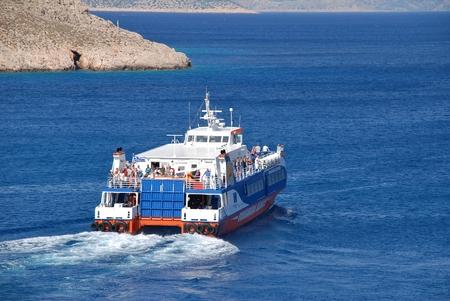 emborio: Halki, Greece - June 16, 2015 - Dodekanisos Seaways catamaran ferry Dodekanisos Express departs Emborio harbour on the Greek island of Halki. The 40mtr vessel was built in 2000 in Norway.