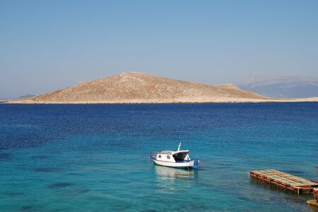 emborio: A small boat moored near Ftenagia beach at Emborio on the Greek island of Halki.  The uninhabited island of Nissos is in the background.