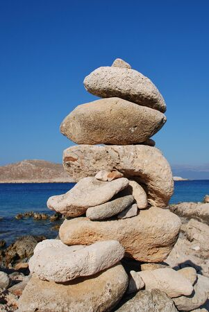 emborio: A tower of stones on Ftenagia beach at Emborio on the Greek island of Halki. The uninhabited island of Nissos is in the background.
