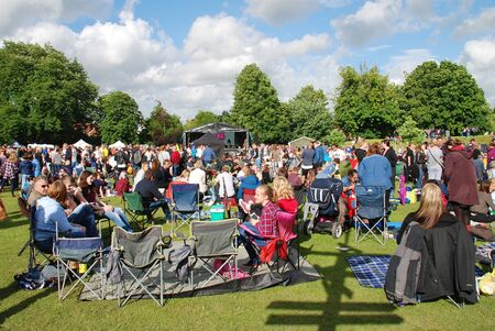 Tenterden, England - July 2, 2016 - the audience sits on the grass during the annual Tentertainment music festival. Held in the public park the free event was first started in 2008.